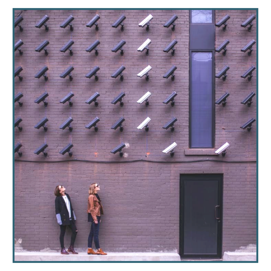 Two young women looking at a lot of security cameras to illustrate the importance of camera surveillance at self-storage facilities