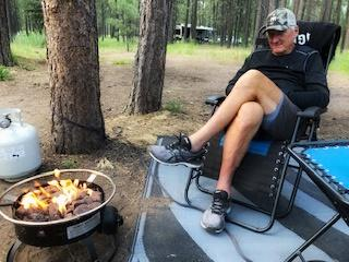 Tom Seibolt sits by fire on RV camping trip
