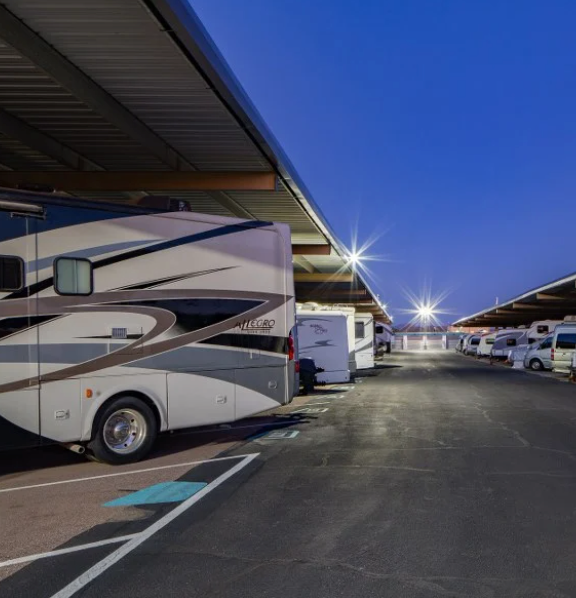 RV's parked at covered well lit lot at night.