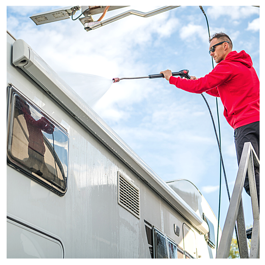Man standing on ladder washing RV with hose.