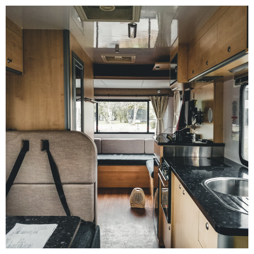 Interior of clean RV showing kitchen and dinette area.