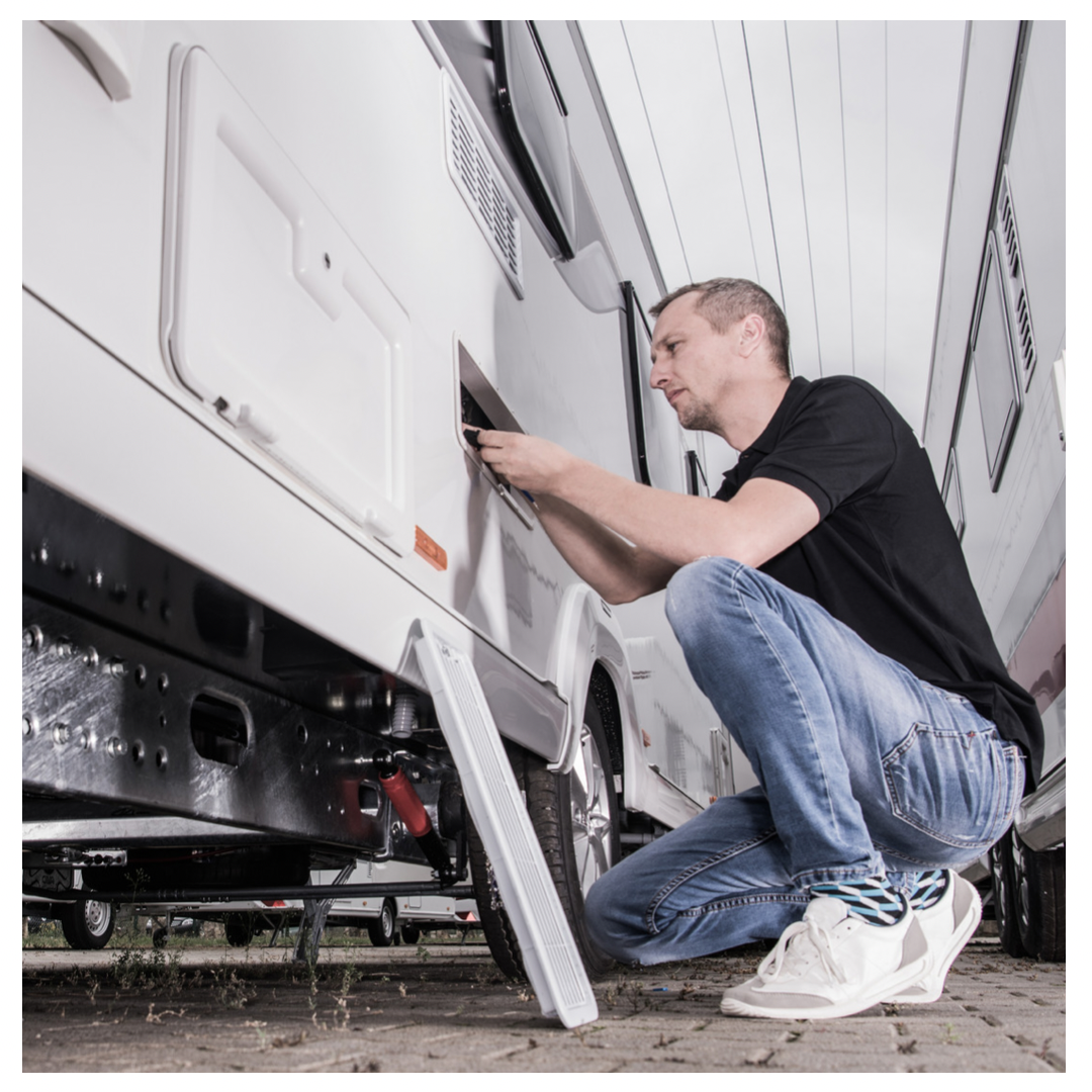 Man disconnecting something behind panel on exterior of RV.