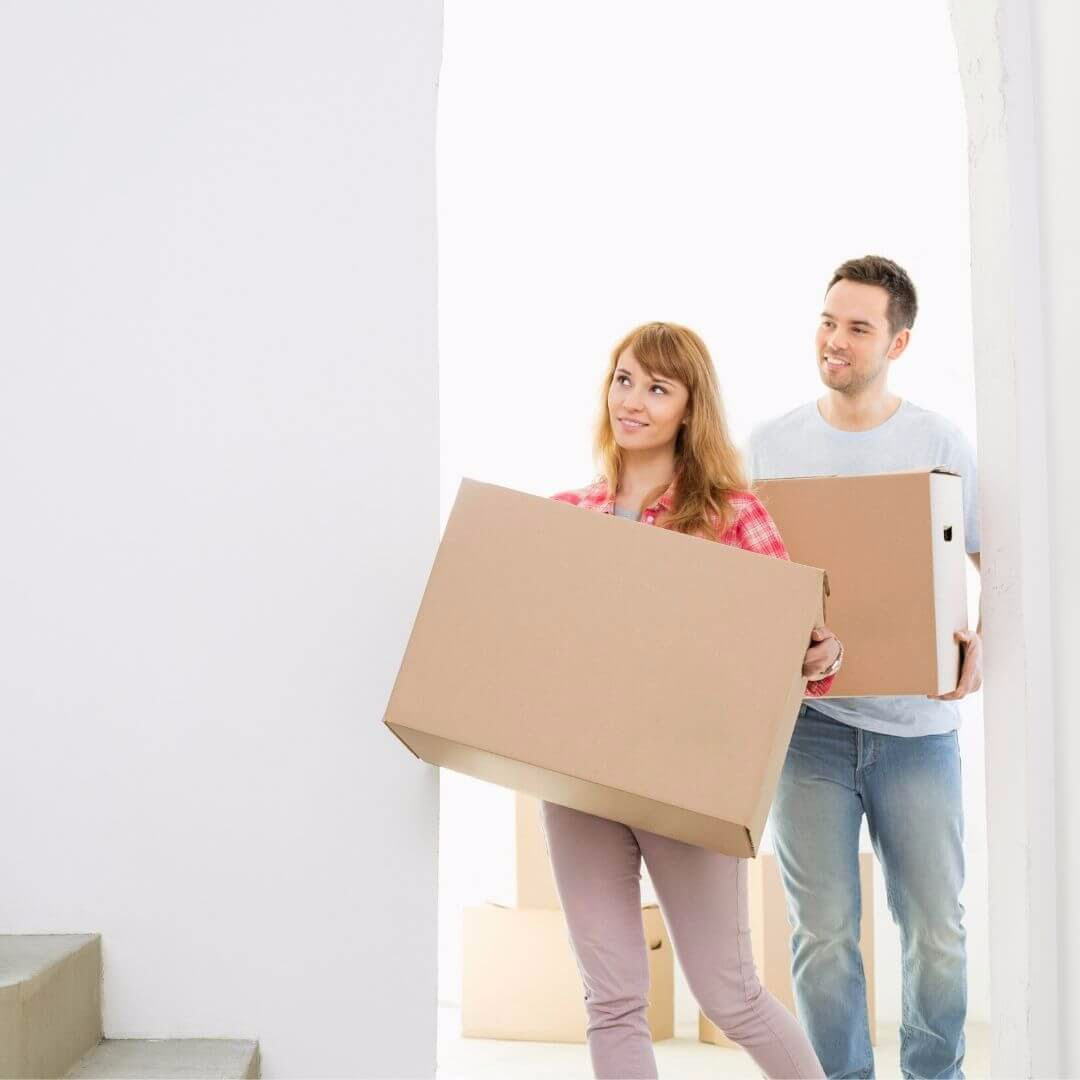 a couple moving into their house with moving boxes