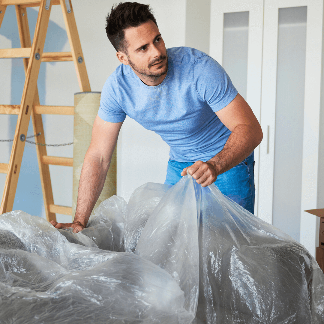 man putting plastic wrap over his furniture